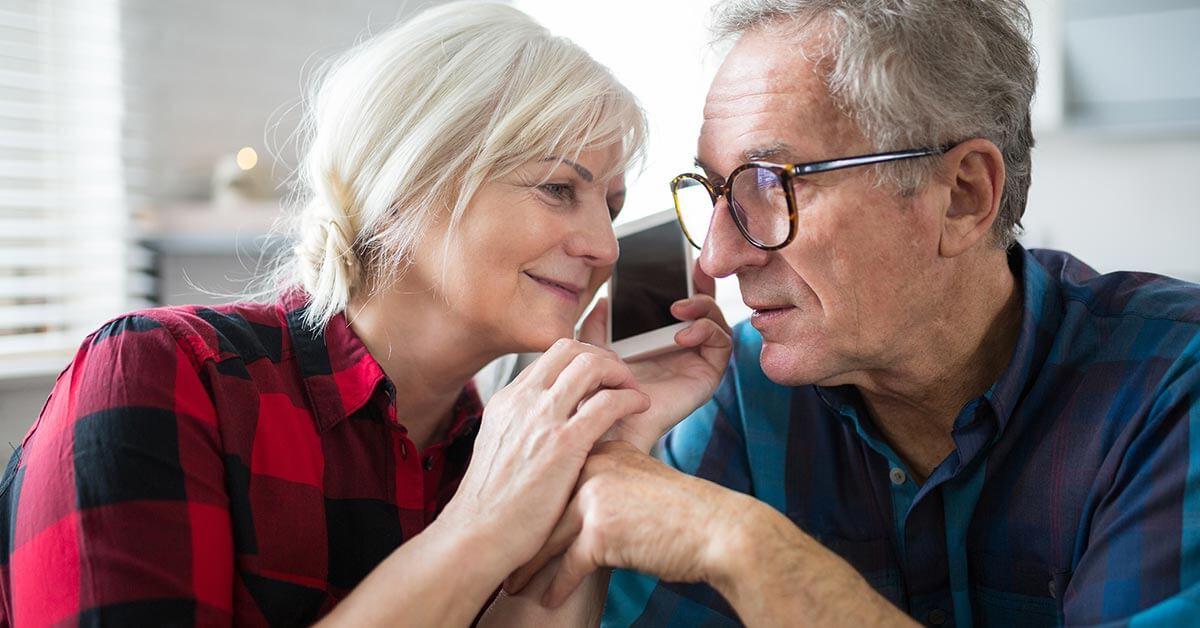 Ein Paar telefoniert gemeinsam mit dem Mobiltelefon
