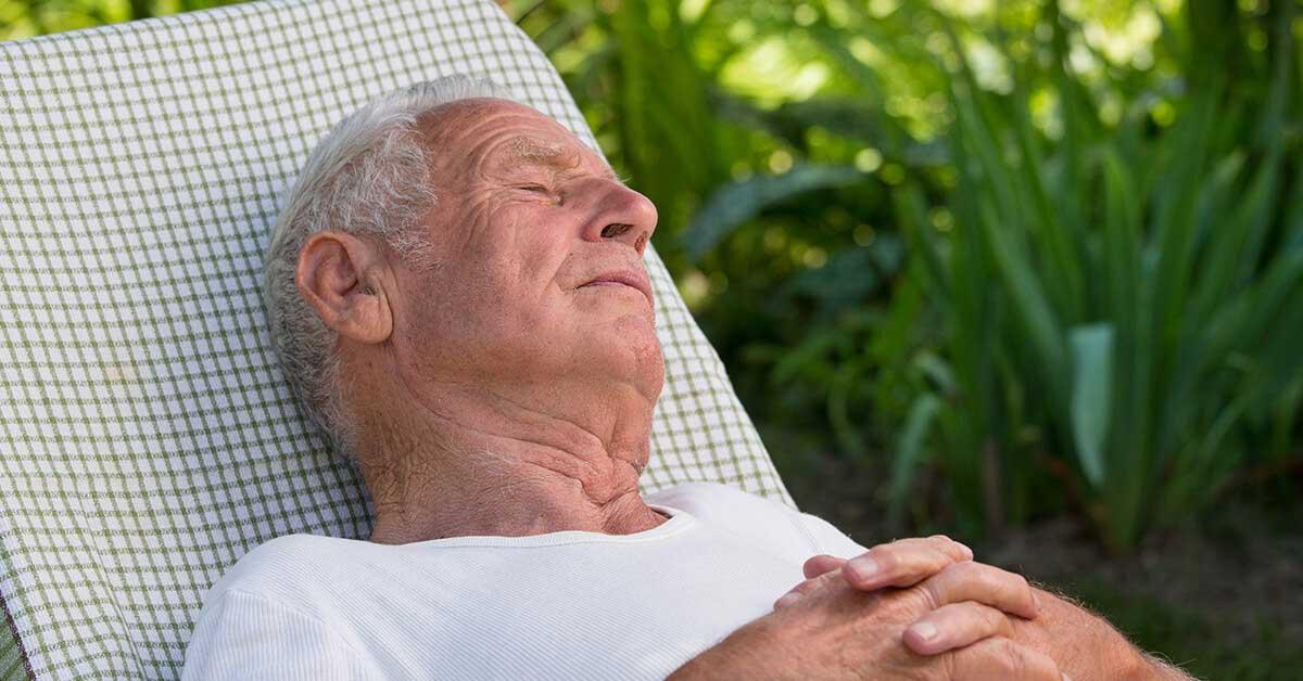 Ein Mann schläft im Garten