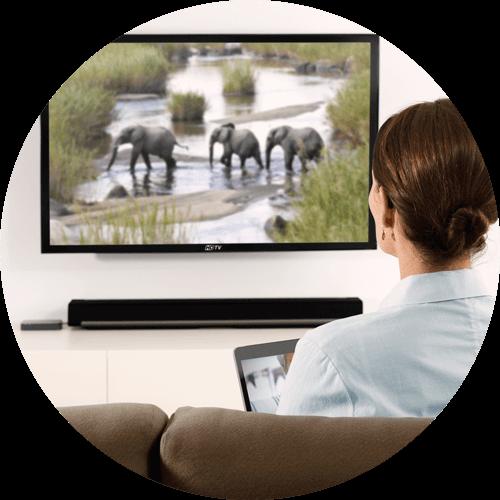 Frau sitzt vor dem Fernseher und schaut eine Dokumentation