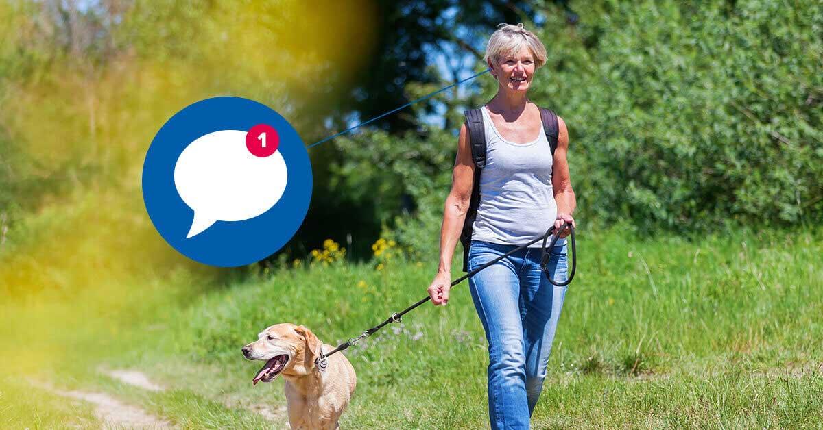 Eine ältere Frau spaziert mit Ihrem Hund