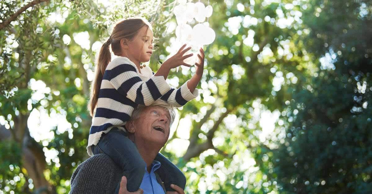 Il nonno tiene in braccio la nipote sulle spalle.