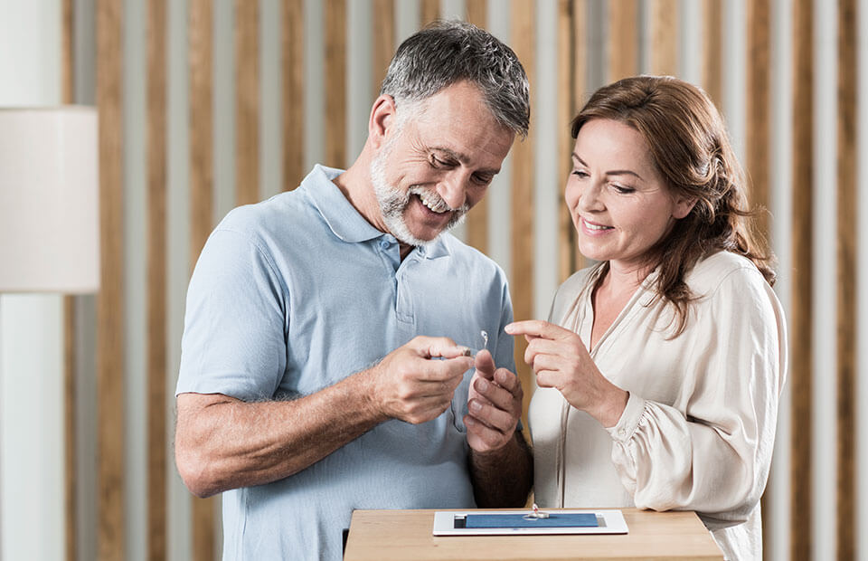 Ein Ehepaar schaut sich die Hörgeräte genau an