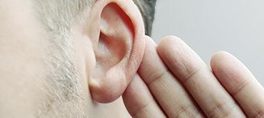 Mann hält sich Hand hinters Ohr