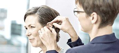 Akustikerin legt einer Kundin ein Hörgerät ans Ohr
