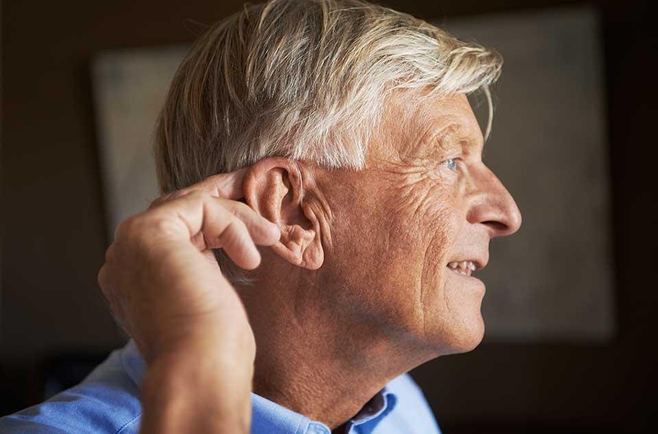 Ein älterer Mann berührt sein Hinter-dem-Ohr-Hörgerät