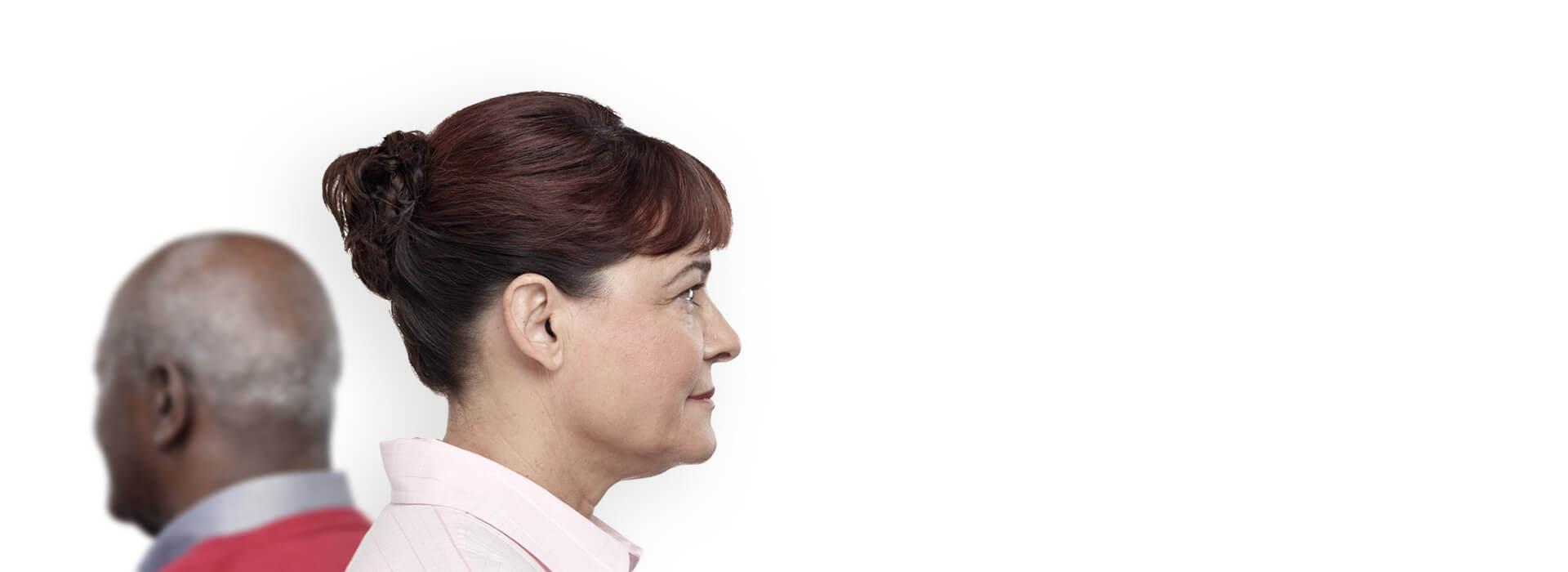 Seitliche Ansicht von einer Frau mit Im-Ohr-Hörgeräten