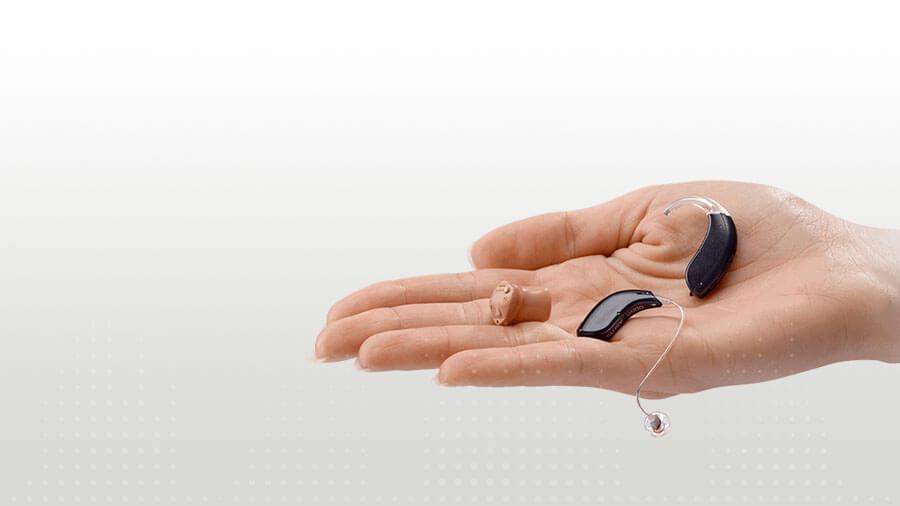 verschiedene Hörgeräte Arten auf der Hand liegend