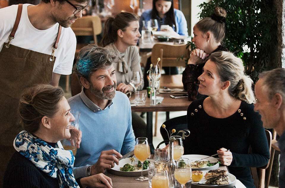 Vier Freunde essen zusammen in einem Restaurant