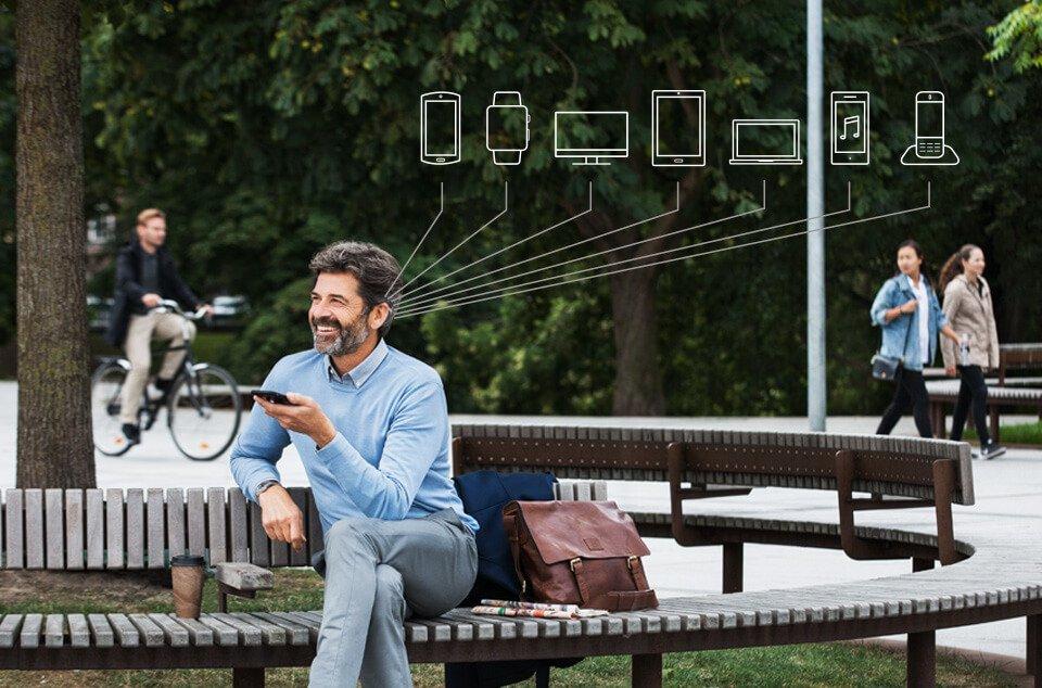 Ein Mann sitzt auf der Parkbank mit seinem Smartphone