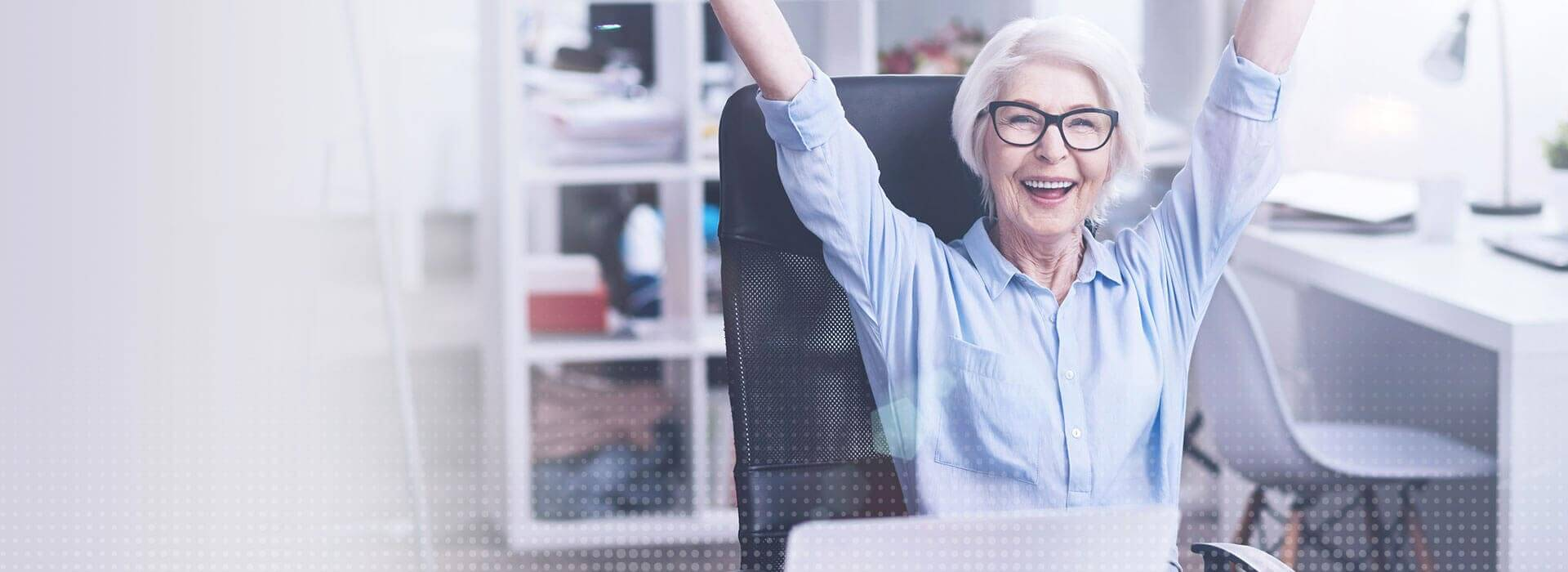 eine ältere Frau im Büro freut sich