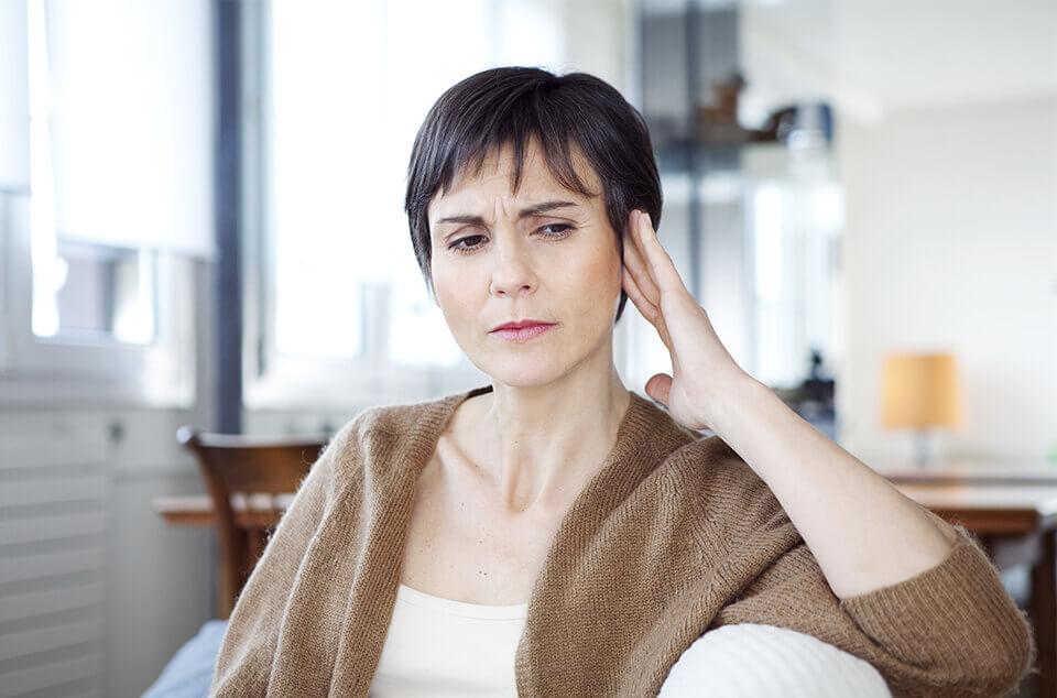 Frau hält sich am Ohr