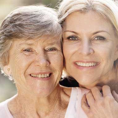 zwei ältere Frauen schauen glücklich in die Kamera