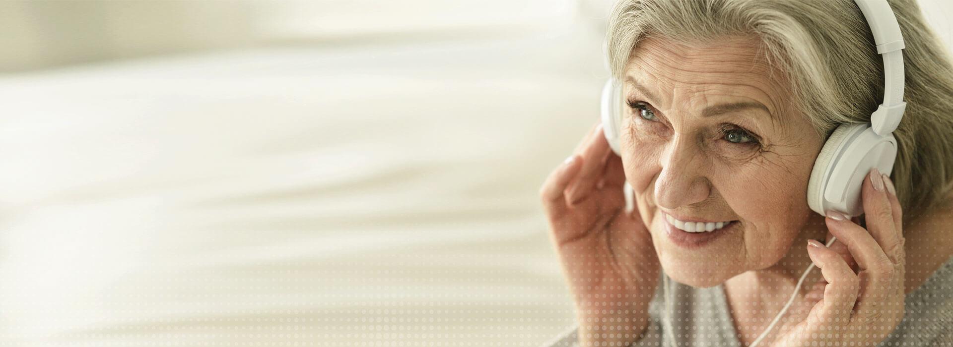 eine ältere Frau hört mit ihren Kopfhörern
