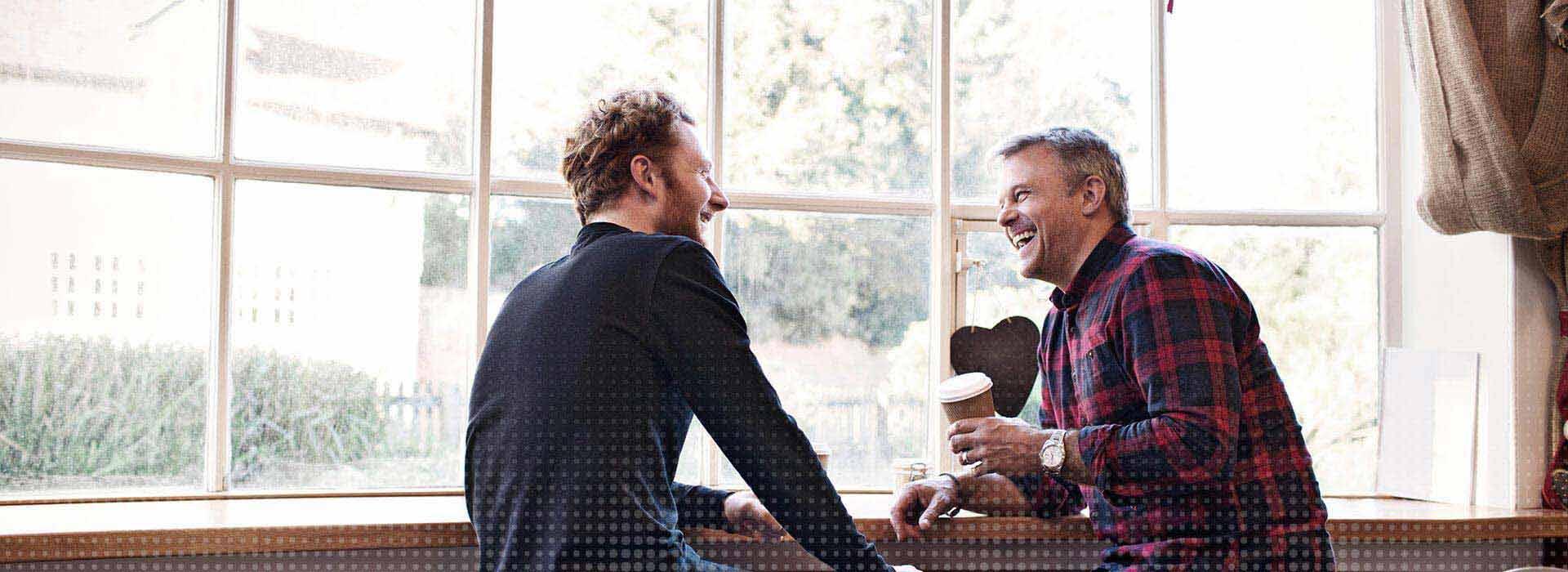 Zwei männliche Freunde sitzen in einem Café