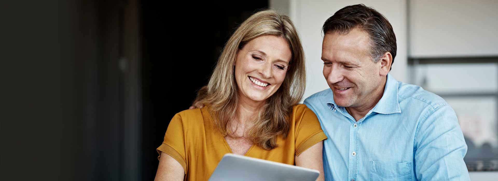 Ein Ehepaar liest etwas auf ihrem Tablet