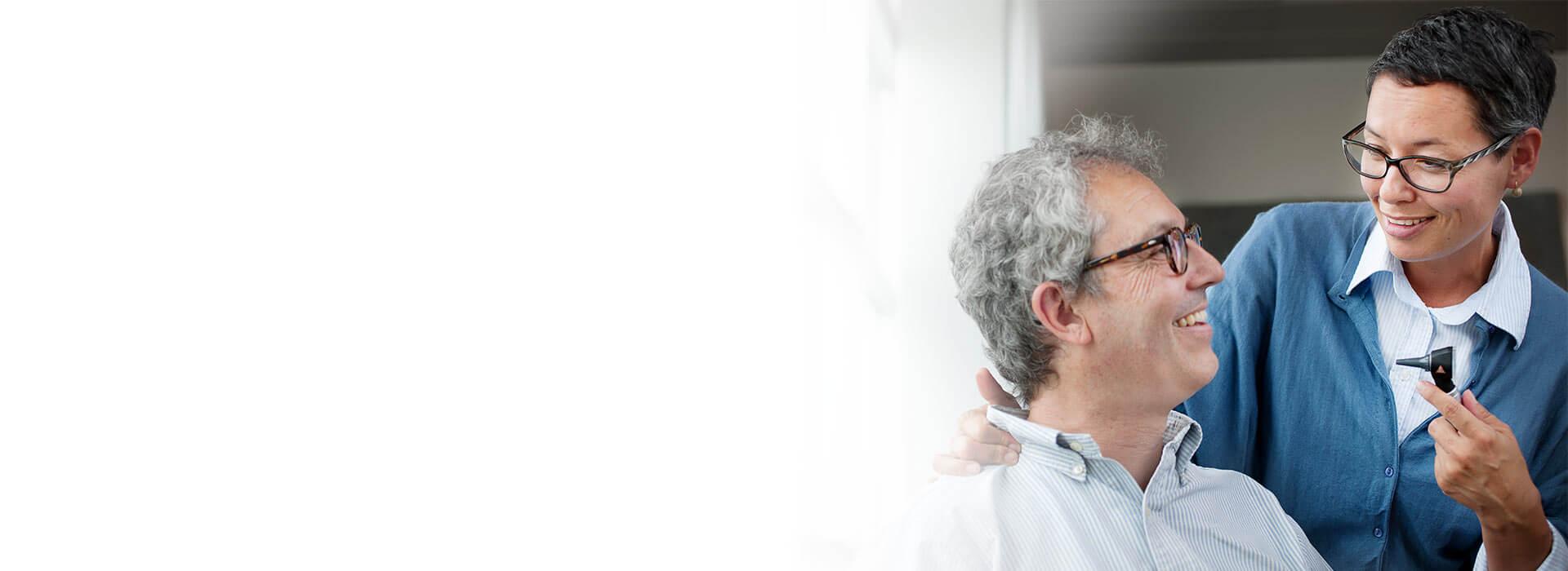 Eine Hörgeräteakustikerin kontrolliert das Ohr eines Kunden