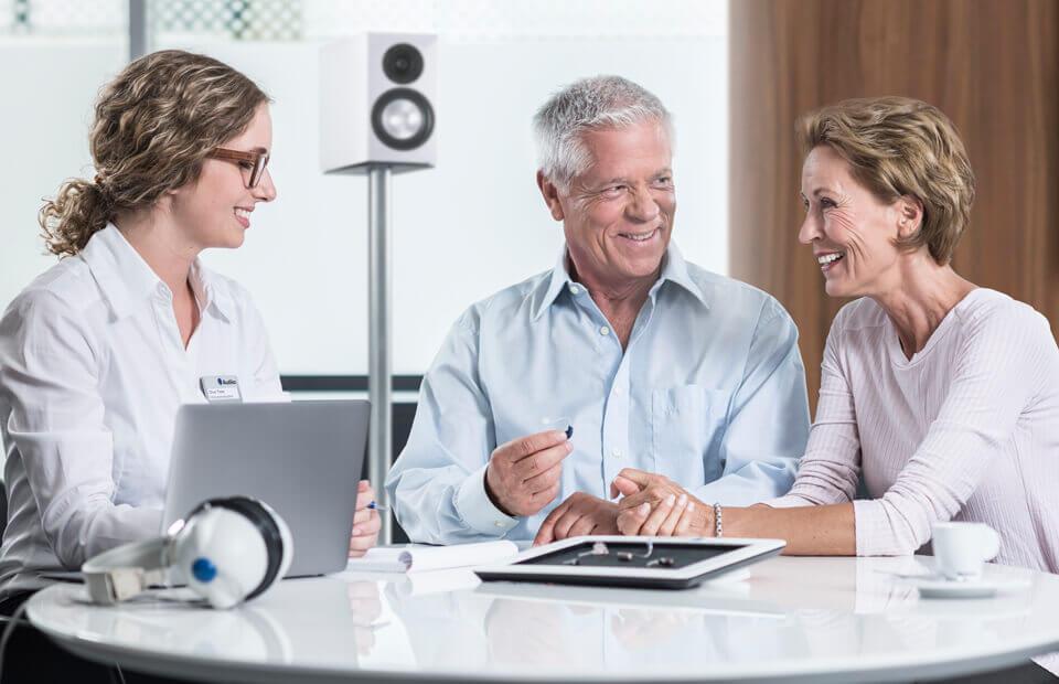 Beratungsgespräch zwischen einem Ehepaar und einer Hörgeräteakustikerin