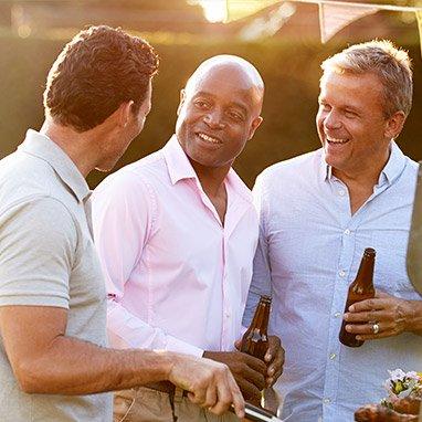Drei lachende Männer beim BBQ