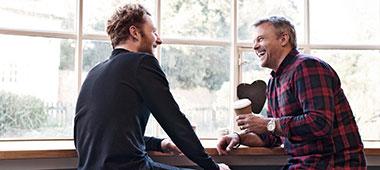 zwei Männer unterhalten sich in einem Café