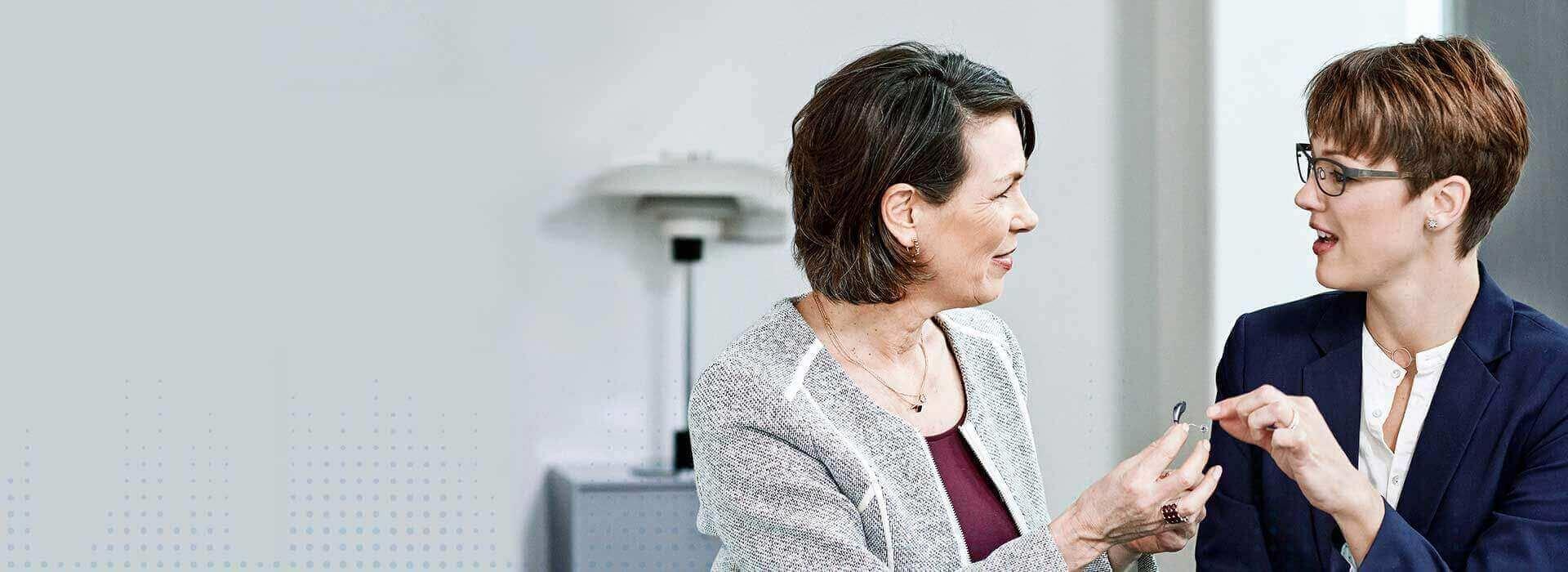 Zwei Frauen schauen sich ein Hörgerät an