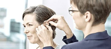 Akustikerin passt ein Hörgerät an