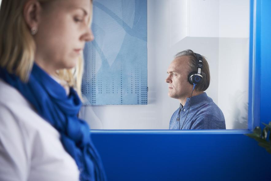 Man in box taking hearing test