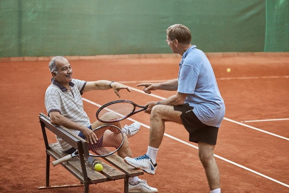 Deux amis retraités discutent après un match de tennis