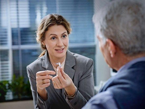 Présentation d'une aide auditive par une audioprothésiste à un patient.