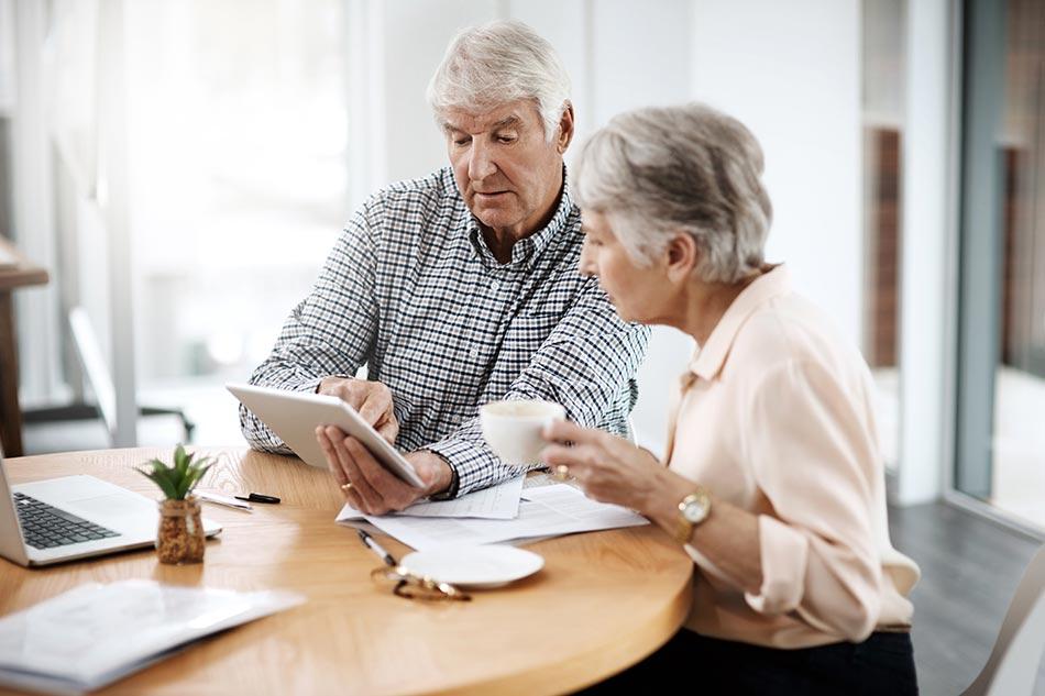 Couple de seniors s'informant sur les tests auditifs en ligne