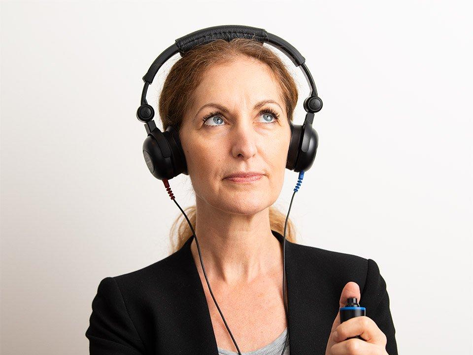 Kvinna gör hörseltest - boka tid för hörseltest och testa hörseln hos Audika - online eller på klinik.