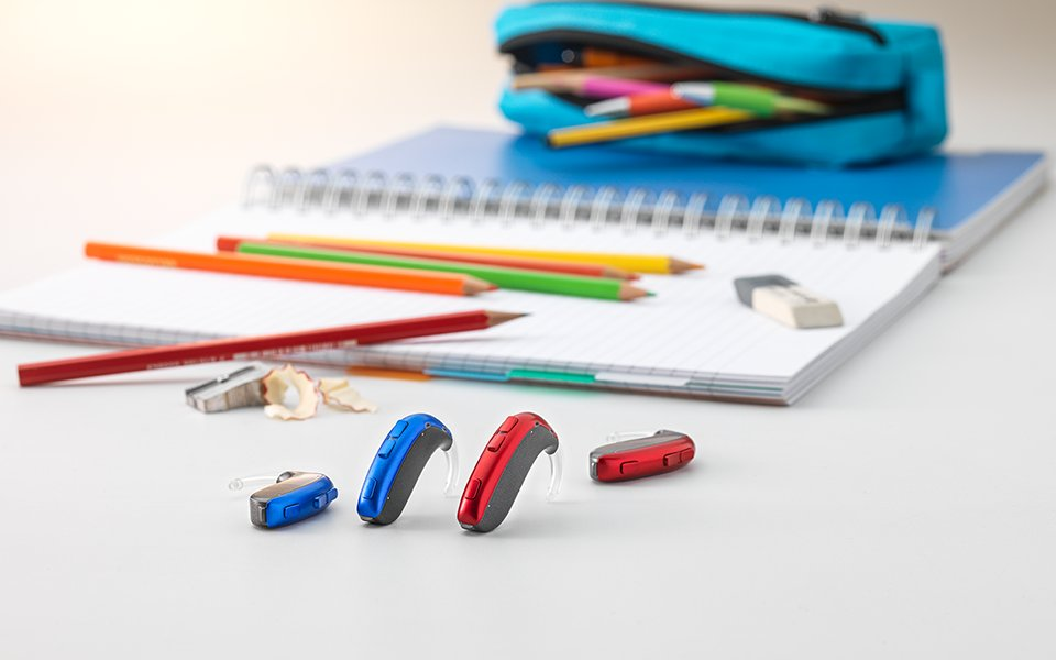 The Bernafon Leox Super Power|Ultra Power behind-the-ear hearing aids in front of colored crayons and other school materials.