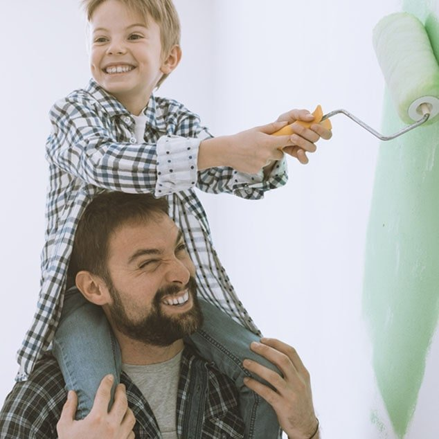 Father carries son with Bernafon Leox Super Power|Ultra Power behind-the-ear hearing aids on his shoulders to paint a wall.