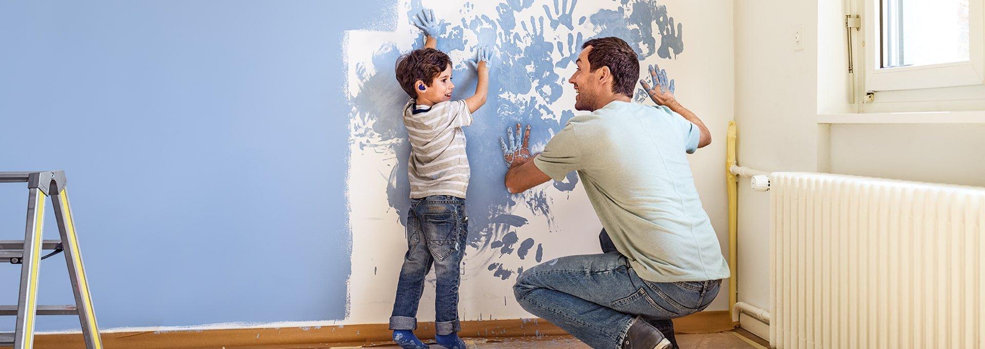 Vader en zoon met Bernafon Leox Super Power Ultra Power hoortoestellen schilderen spontaan een muur en voegen handafdrukken toe.