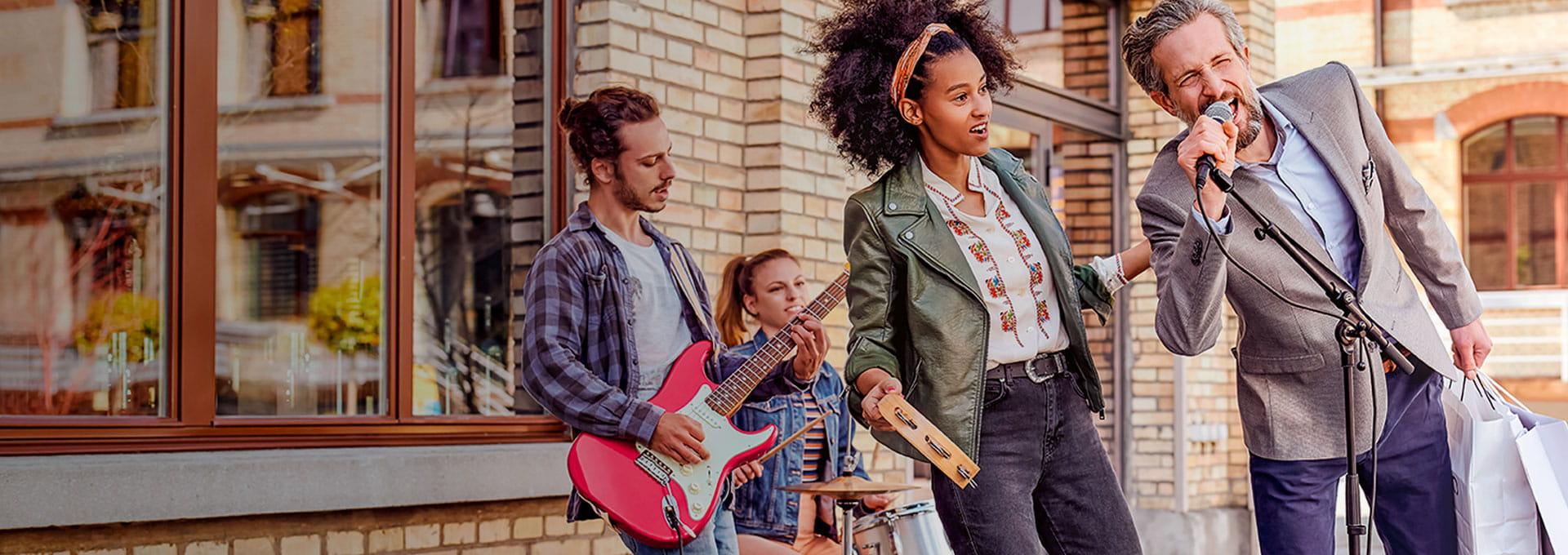 man met Bernafon Leox Super Power Ultra Power achter-het-oor hoortoestellen spontaan aan het zingen met een band op straat.