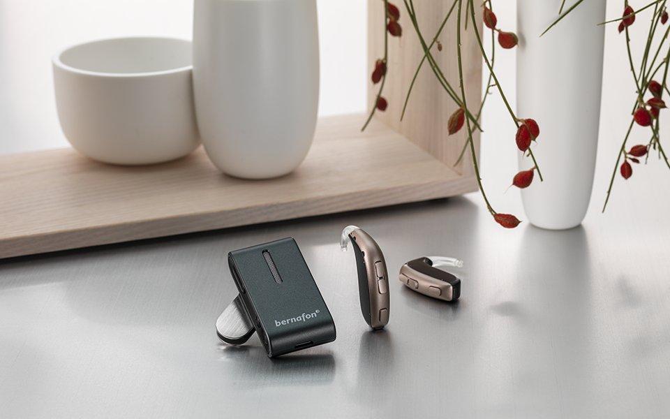 El Bernafon Leox Super Power|Ultra Power detrás de la oreja y un SoundClip-A delante de un jarrón y un marco de madera.