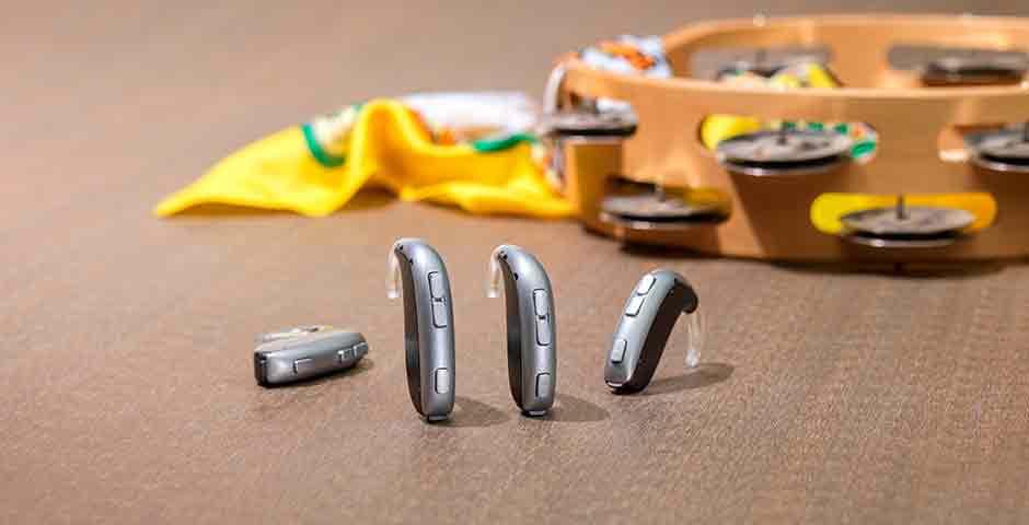 Gli apparecchi acustici Leox Super Power Ultra Power di Bernafon davanti a un tamburello e ad una sciarpa gialla.