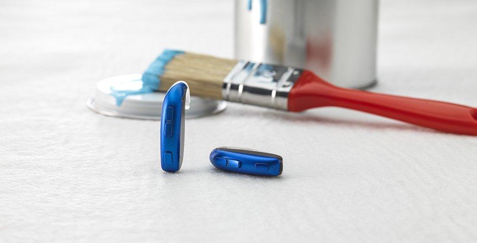 Los audífonos Bernafon Leox Super Power | Ultra Power detrás de la oreja con un pincel rojo y una lata de color azul.
