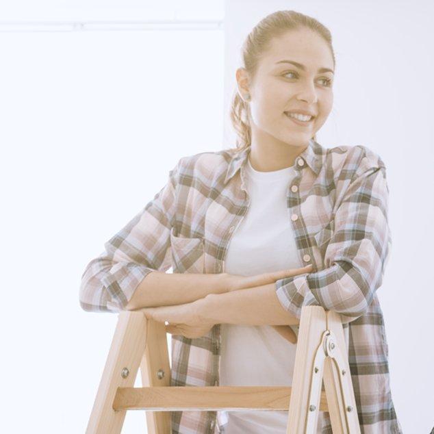 Lächelnde Frau mit Bernafon Leox Super Power|Ultra Power Hörgeräten beobachtet ihre Familie beim Renovieren und steht auf einer Leiter.