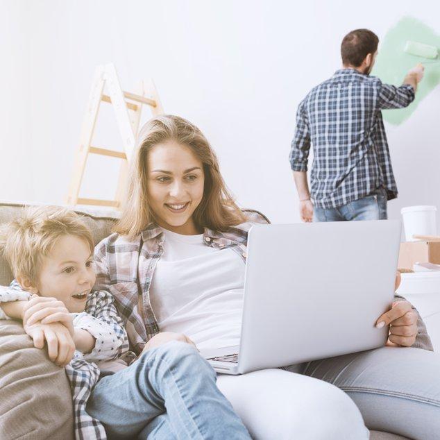 Mutter und Sohn mit Bernafon Leox Super Power|Ultra Power Hörgeräten sehen auf einen Laptop, während der Vater eine Wand streicht.
