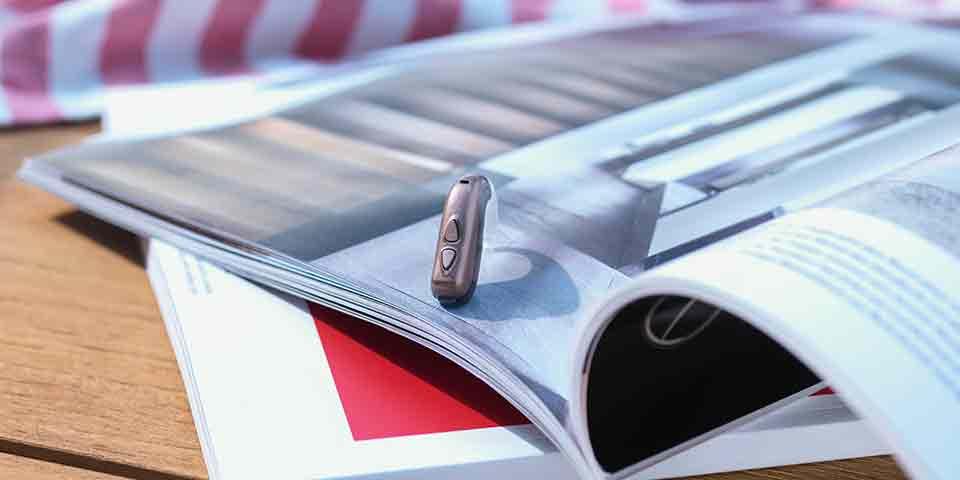 Det nye Bernafon Viron BTE høreapparat på et udendørs bord med et arkitekturmagasin.