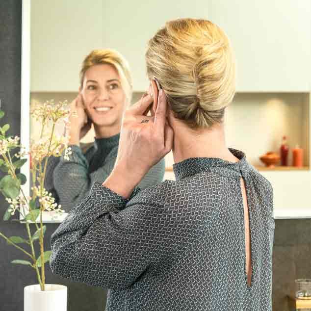 Eine Frau macht sich vor einem Spiegel zurecht und setzt ihre wiederaufladbaren Hörgeräte miniRITE T R ein.