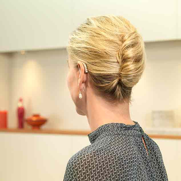 Woman at home seen from behind wearing her Bernafon Viron miniRITE T R rechargeable lithium-ion hearing aids.