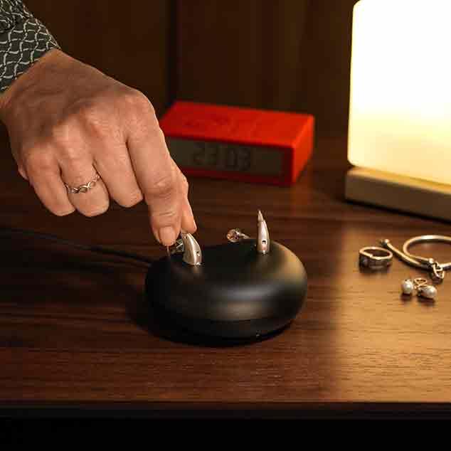Kobieta wkładająca aparaty Viron miniRITE T R z baterią litowo-jonową do ładowarki na stoliku nocnym.