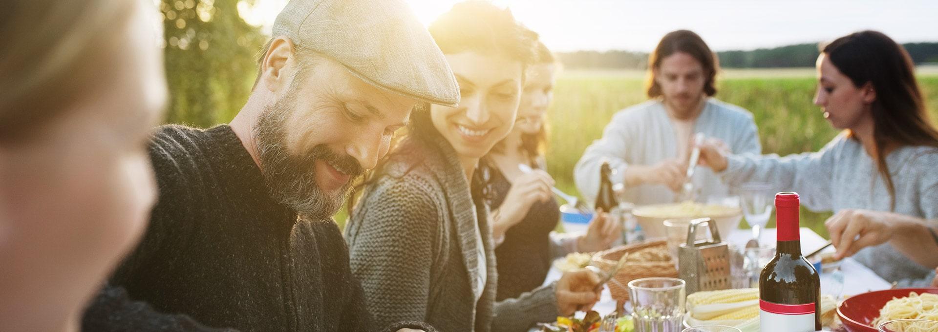 Eine Gruppe von Menschen machen im Freien ein Picknick um einen Tisch herum in einer geräuschvollen Umgebung.