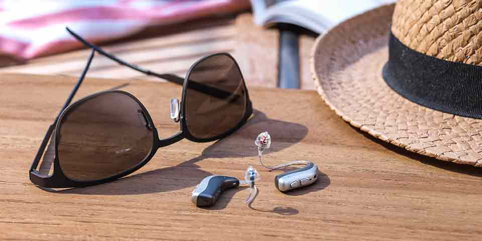 New Bernafon Viron miniRITE T R lithium-ion rechargeable hearing aids lying on an outdoor table next to a hat and sunglasses.