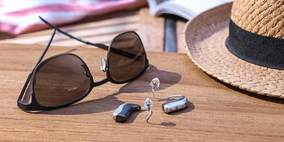 Nuevos audífonos Bernafon Viron miniRITE T R recargables con batería de litio  sobre una mesa al aire libre junto a un sombrero y gafas de sol.