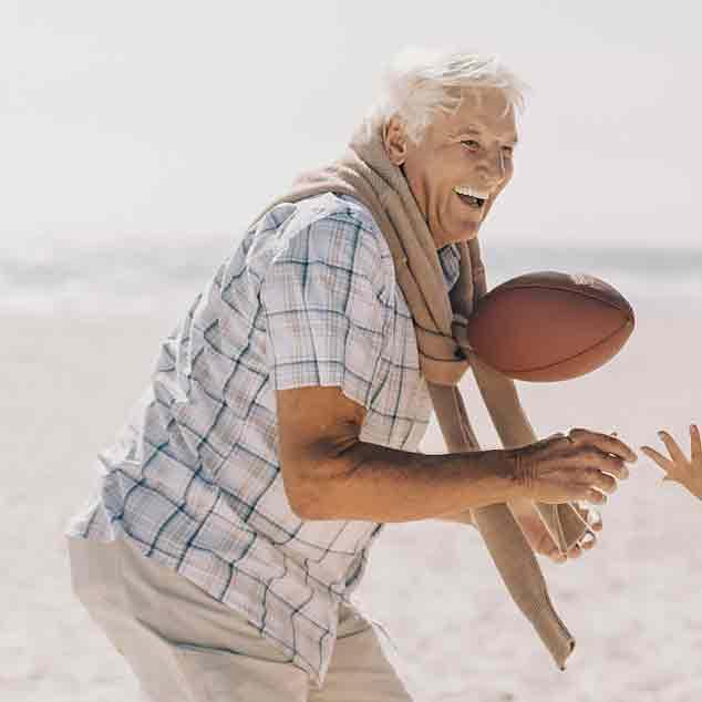 Używający aparatów słuchowych Viron dziadek grający na plaży w rugby z rodziną i cieszący się momentem.