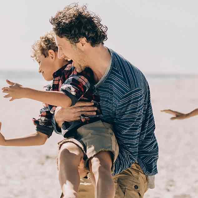 Padre in spiaggia con la famiglia che tiene in braccio il figlio giocando a rugby e godendosi il momento.