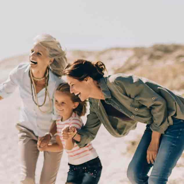 Oma, moeder en dochter op het strand, spelen rugby met de familie en maken plezier.