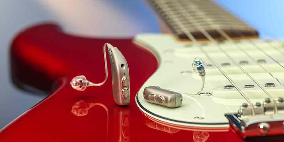 De nieuwe Bernafon Viron miniRITE T R lithium-ion oplaadbare hoortoestellen op een rood electrische gitaar.